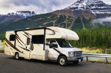 RV drives along in front of a mountain range.